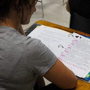 Female student reading notes in a three ring binder