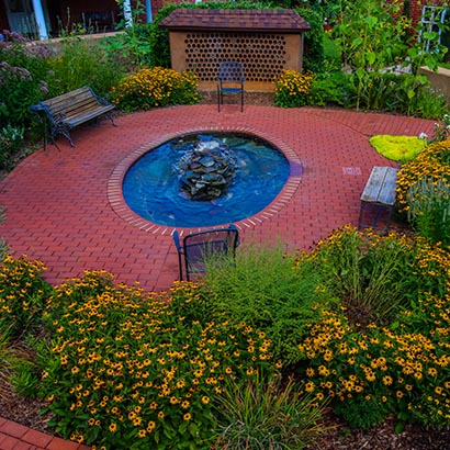 Garden with red brick walkways, a blue fountain, and green shrubs