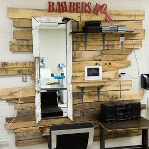 Barber station with a black chair and hair cutting supplies
